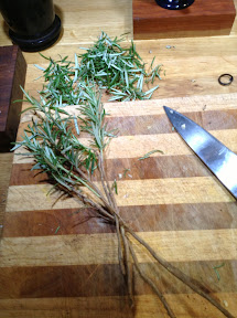 Four rosemary sticks and a pile of rosemary leaves on a chopping board, knife next to them
