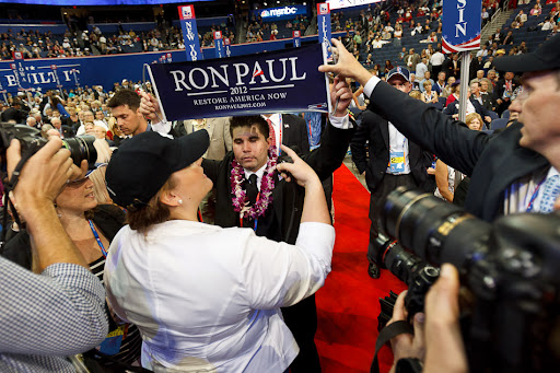 A Ron Paul banner is pulled away from delegate Braedon Wilkerson on the first day of the Republican National Convention