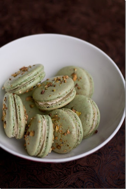 A white bowl full of Pistachio macarons topped with pistachios.