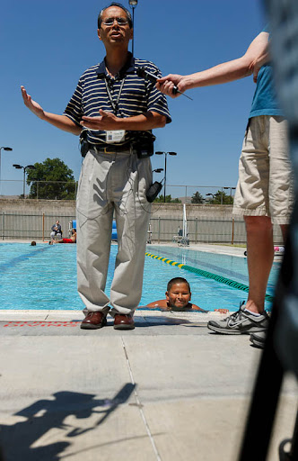 Rick Ledbetter, Environmental Health Supervisor for the Salt Lake Valley Health Department, urged residents to defend themselves against waterborne illnesses at a press conference at the Liberty Park pool. In the pool behind Ledbetter is Ruben Saldivar.