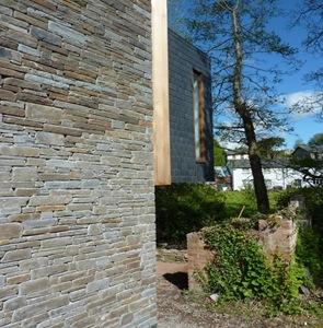 fachada de casa rustica con madera y piedra vista