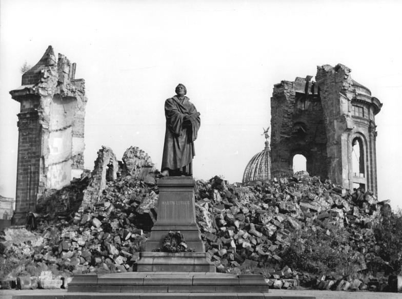 Уцелевший памятник Мартину Лютеру перед развалинами церкви Фрауэнкирхе