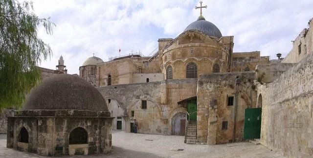 Vista de la Basílica del Santo Sepulcro desde el patio del monasterio etíope. A la izquierda de la foto se ve la cúpula de la capilla de Santa Elena (en la parte baja) y de la capilla de Melquisedek sobre el Calvario (en la parte alta). Al centro, con la cruz, la cúpula delCatholicon