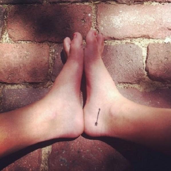 small arrow tattoo design on foot women