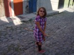 Nadia playing with a broom stick on an empty street.