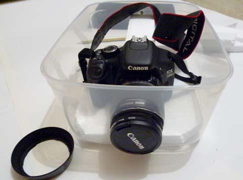 Una reflex dentro un contenitore da frigo con l'obiettivo che sporge da un foro praticato su di un lato.