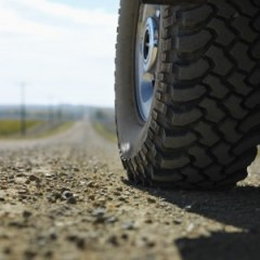 Low angle view of big truck tire on gravel road in rural South Dakota.