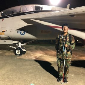 A young man poses in military fatigues next to a jet while attending Space Camp at the U.S. Space and Rocket Center in Huntsville, AL.