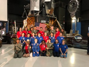 Space Camp attendees sponsored by the Lighthouse for the Blind in 2018 pose in front of a rocket.