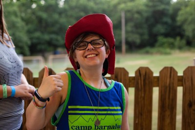 A young girl enjoying herself at Camp Barnabas gives the thumbs up sign.