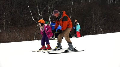 A child who is visually impaired snow skies down a mountain at Hidden Valley Ski Resort