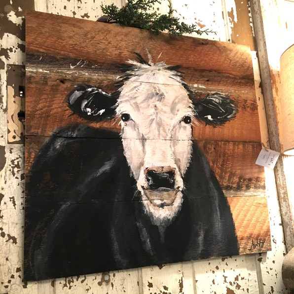 rustic painting on wood board featuring a black and white cow