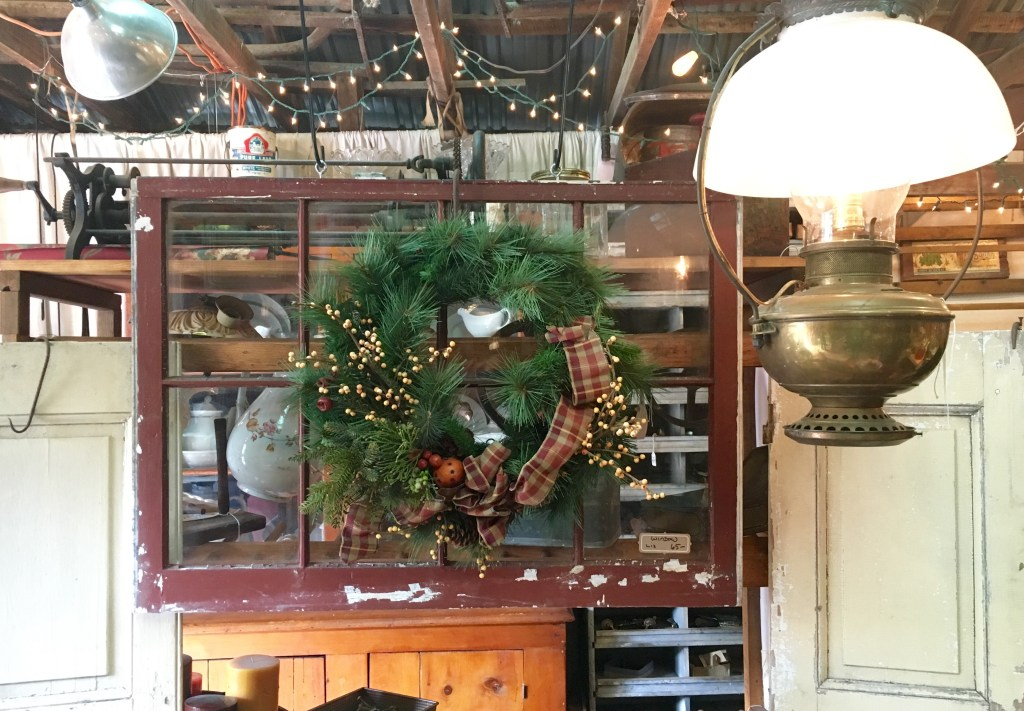 holiday display featuring a christmas wreath in front of salvaged window