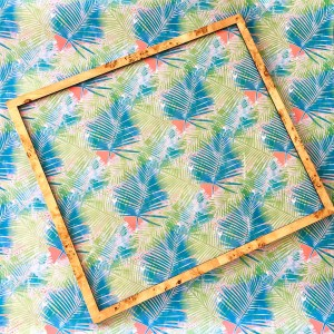 A tropical print, featuring teal and green palm leaves against a peach background, is finished in a simple wood burl frame.