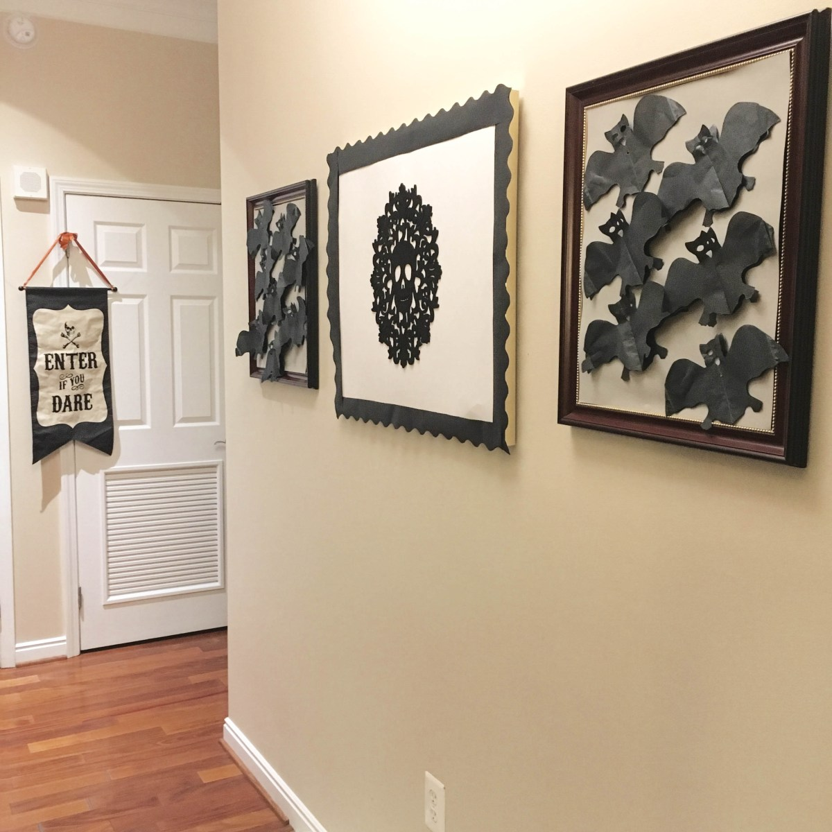 Paper bats flutter on two framed paper pieces, while a skull design is highlighted in the center.