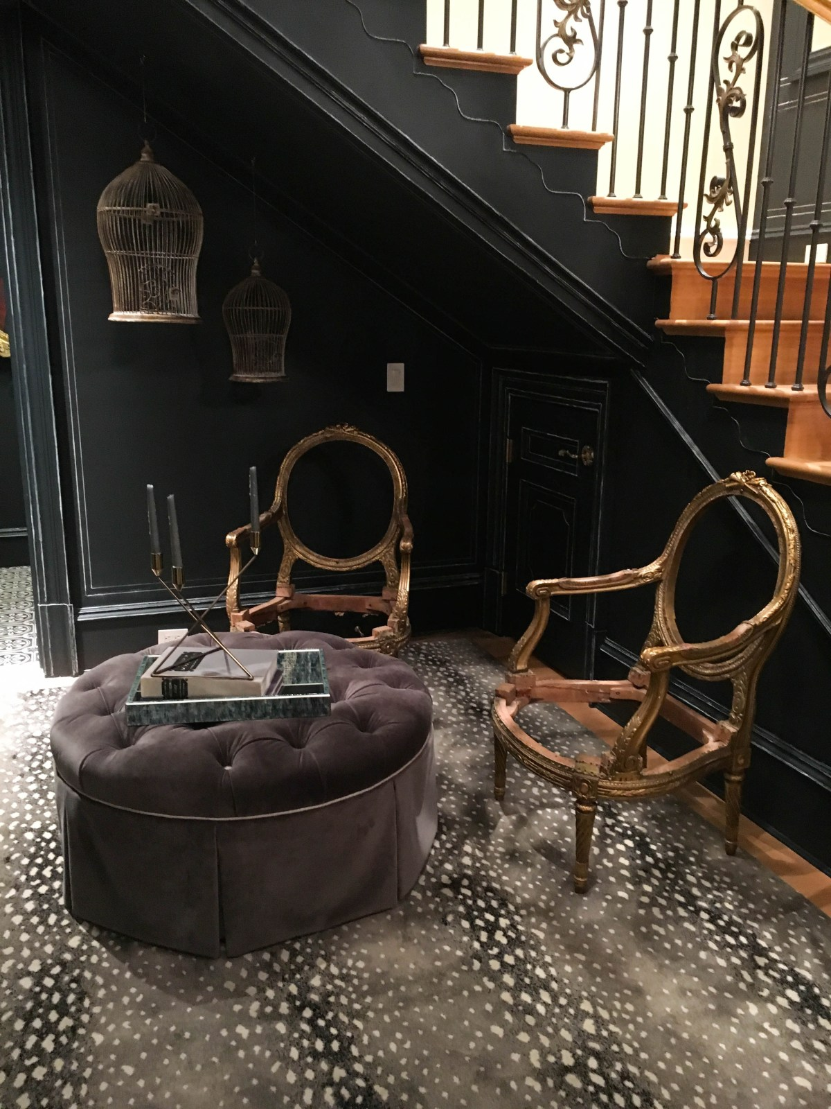 A dark colored and moody space at the bottom of a back staircase stands out for its chalkboard painted walls and Louis XVI chairs displayed without their upholstery.