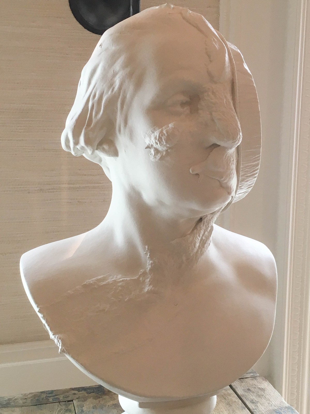 A white plaster bust depicts George Washington with a pie splattered across the side of his face.