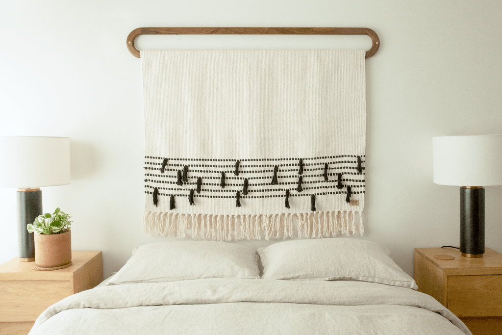 Gorgeous handwoven white blanket with black detailing and fringe hangs above a bed becoming a chic alternative to a traditional headboard.