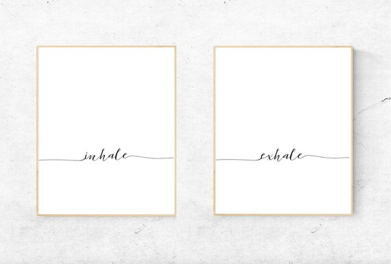 Two white prints hanging side by side with one featuring the word Inhale and the other featuring the word Exhale in a beautiful script font