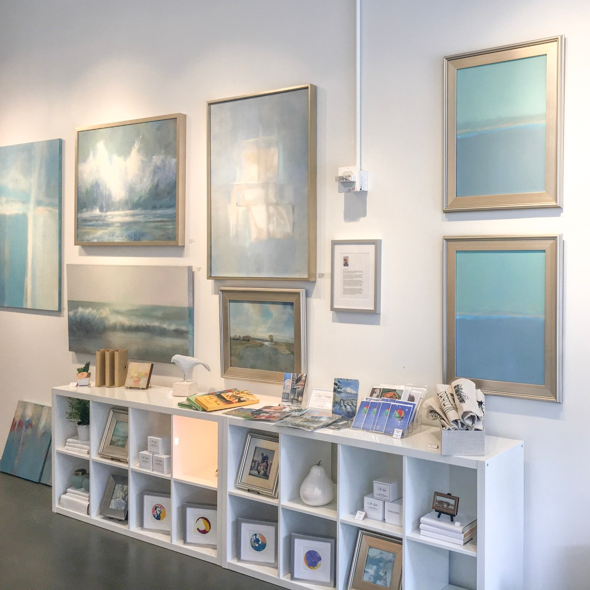 A white gallery wall showcases the cool blue tones of beach inspired paintings by Martha Spak