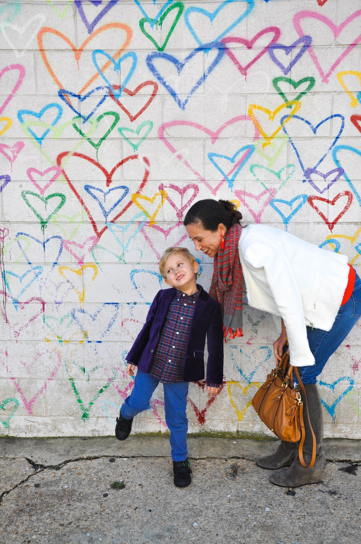 A mother and her young son pose before a DC area mural composed of the outlines of multi-colored hearts.