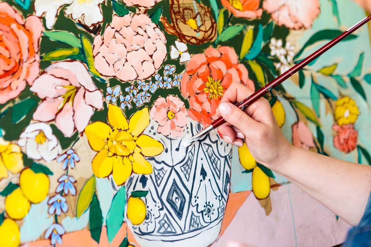 A close up photograph of the artist's hand deftly applying a dab of white paint to a colorful floral composition