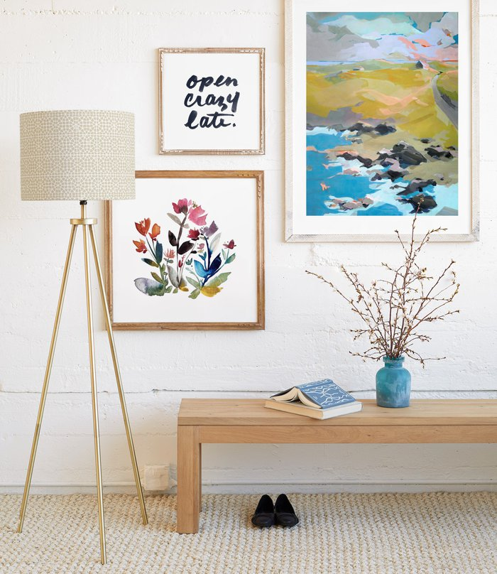The wall in a bright front entryway displays three framed art prints above a wooden bench.