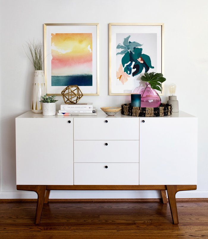 Two colorful modern art prints are framed in matching gold frames, creating an elegant look over this console.