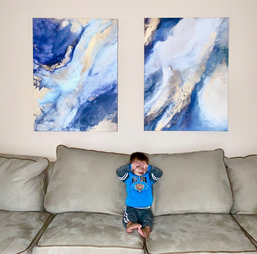 Blue and Gold Marbled Prints Above Sofa with Young Boy Rubbing Eyes