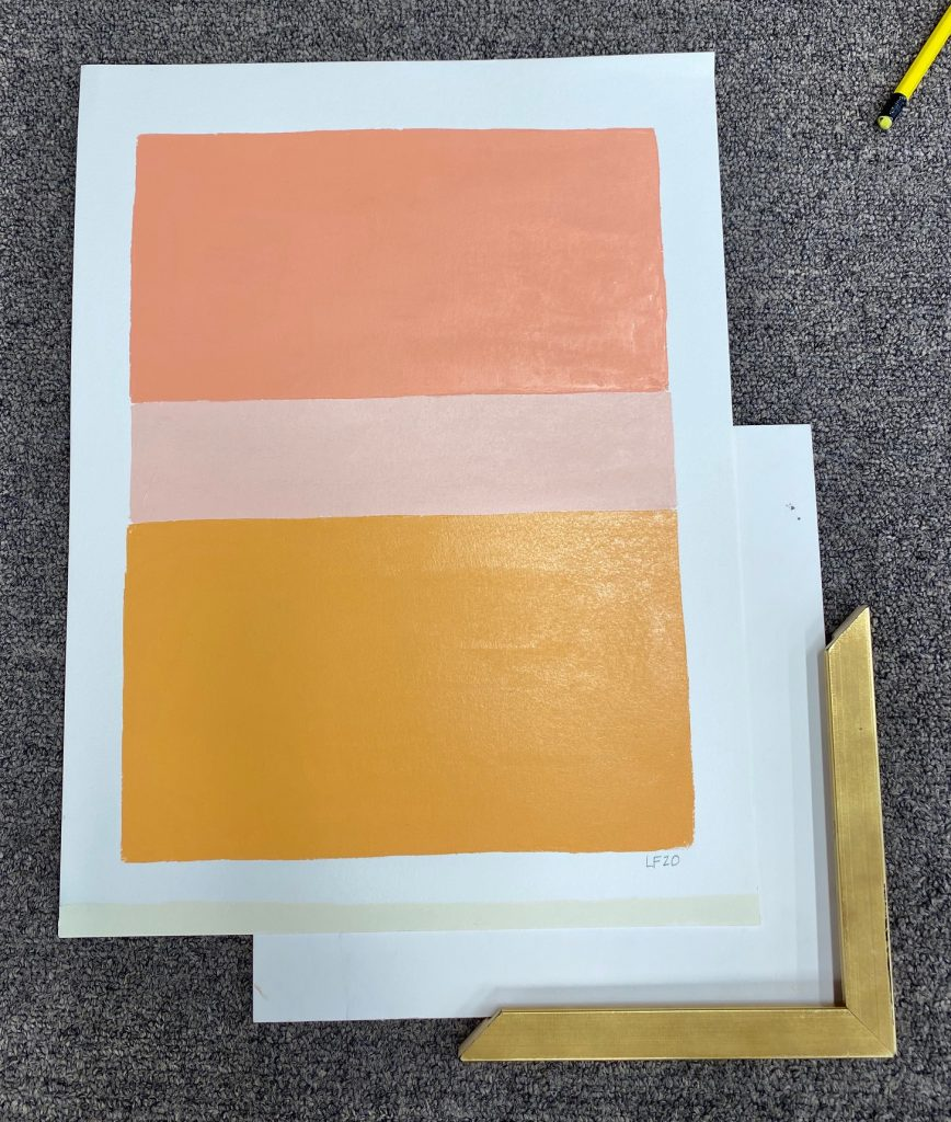 An original painting by artist Laurie Fisher is shown with a corner sample of gold moulding and white matting as an idea for custom framing.