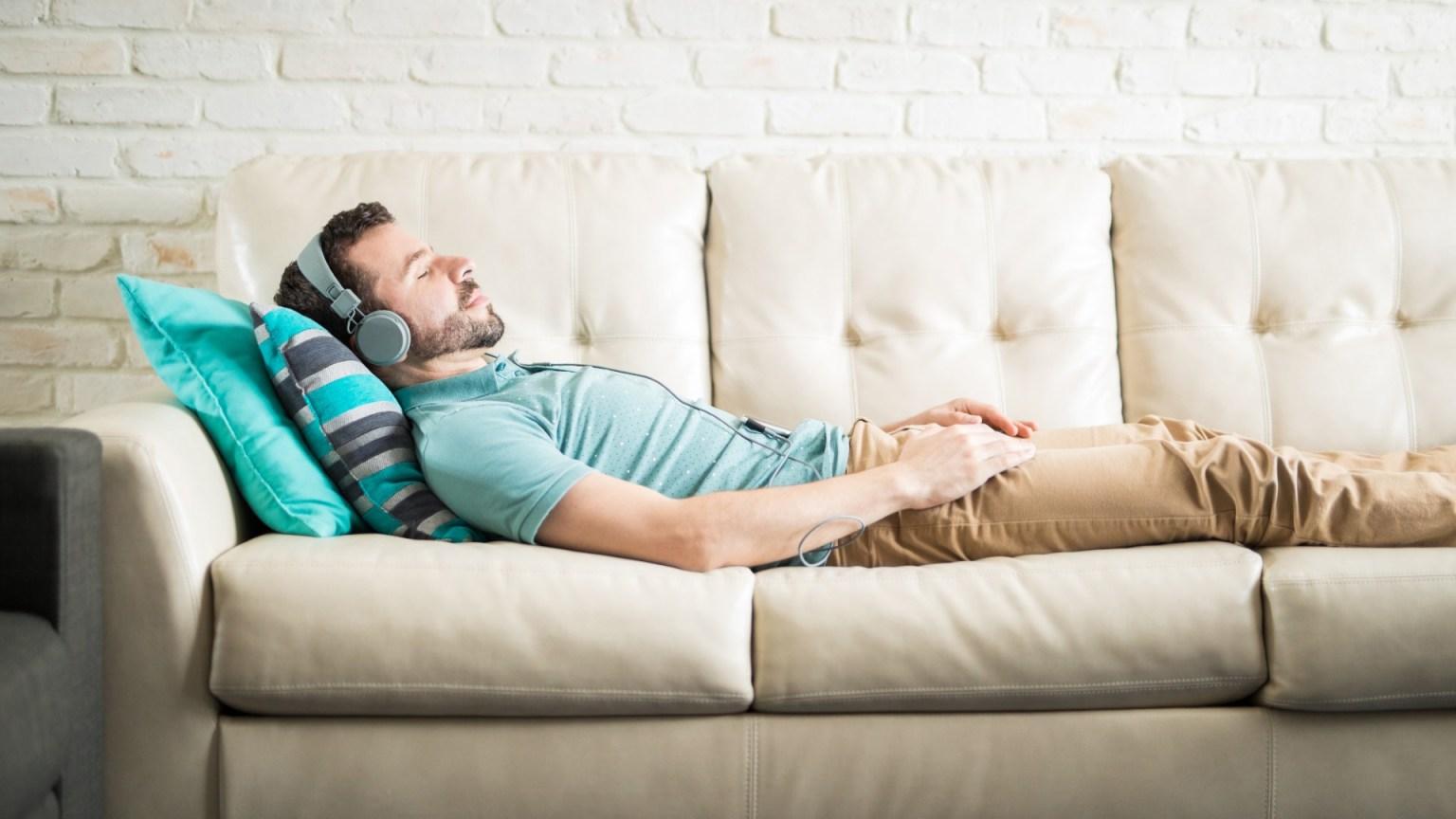 Muž odychujúci na gauči
