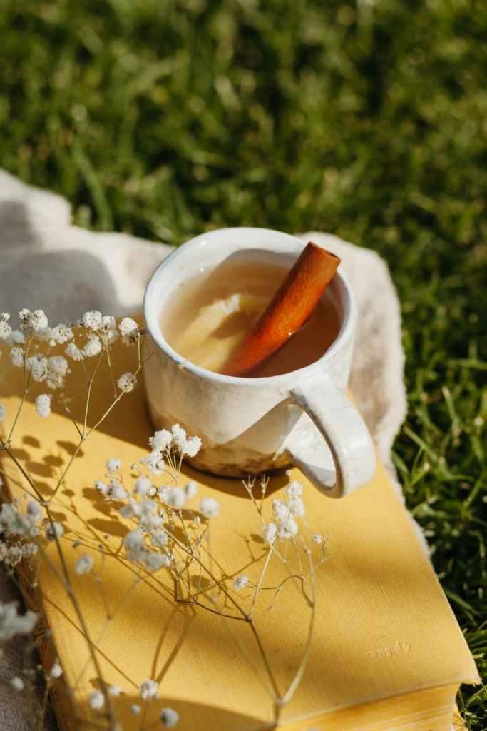 white ceramic mug with brown liquid on yellow textile