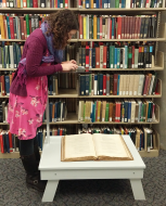 UC Digital Archivist Eira Tansey digitizes a book using her smartphone.