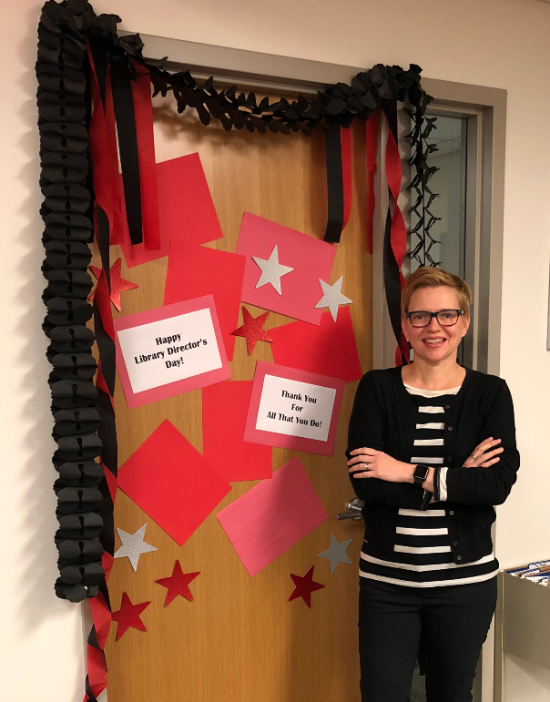 Heather Maloney in standing in front of her decorated office door.