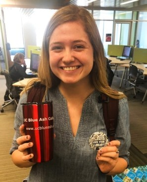 student button contest winner, Sarah Burton, poses with her prize and winning button design