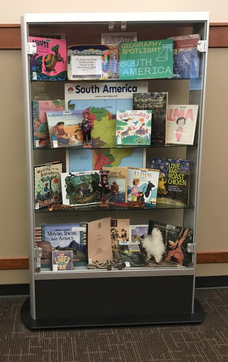 Picture of display case filled with books and materials for children with South American themes