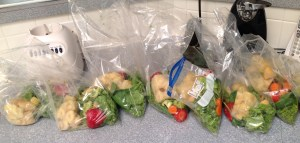 Bags of bananas, strawberries, kale, avocado, cucumbers, carrots, and ginger