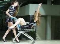 ショッピングカートに女性を乗せて歩く女性