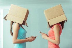 箱をかぶって携帯を見る2人の女性
