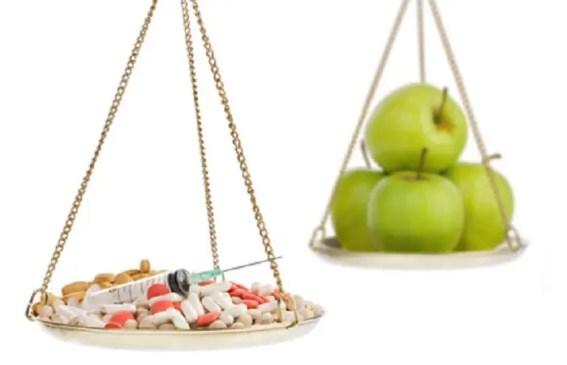 bilancia con un lato piano di medicine l'altro con frutta