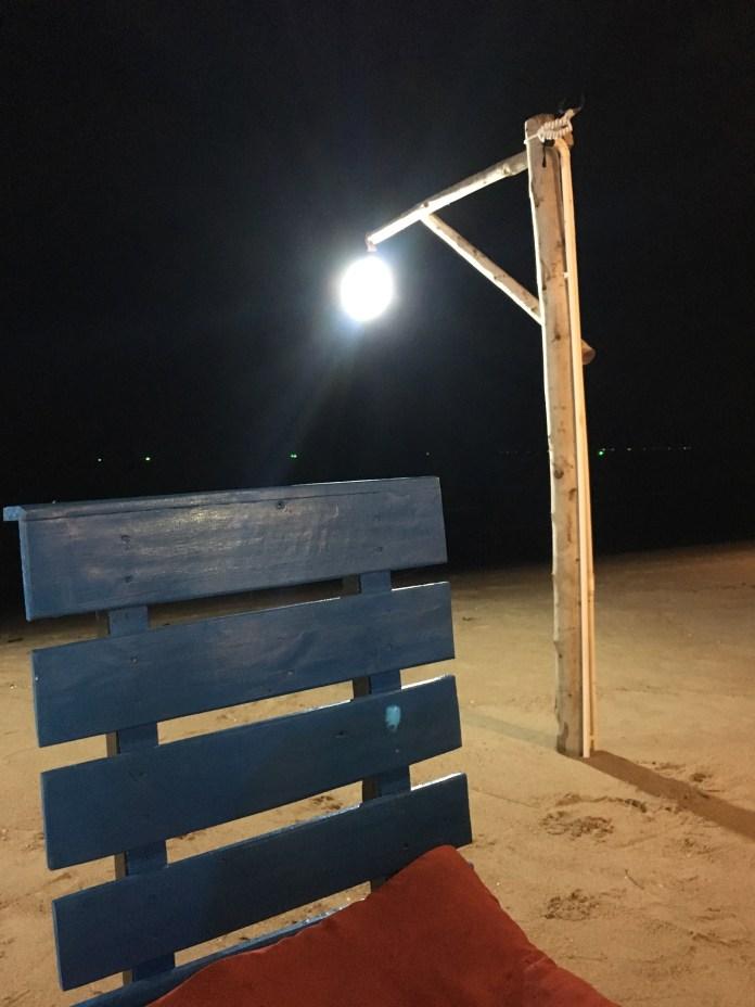 Tuoli ja lamppu pimeällä rannalla.