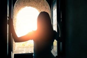 woman opens window onto bright light