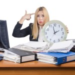overworked author at desk with clock