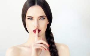 girl with finger across lips to ask for silence
