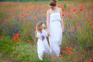 Mother and child hold hands in field of poppies - royal wedding
