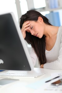 woman at computer screen looking beaten