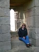 Melinda Hammond sits in window of Dunstanburgh