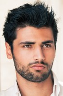 handsome dark-haired young man with beard and faraway gaze