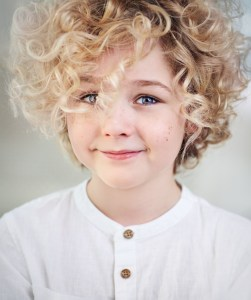 portrait of beautiful happy blonde boy with curly hair