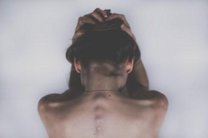 femme sui a mal à sa colonne vertébrale